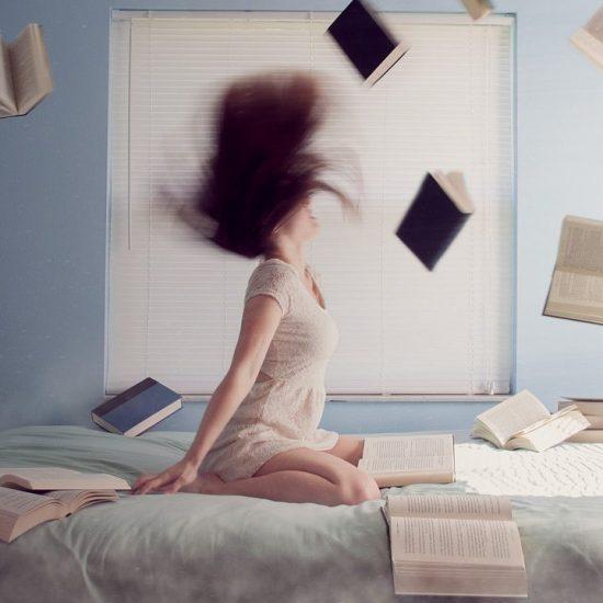 donna in ginocchio sul letto circondata da libri