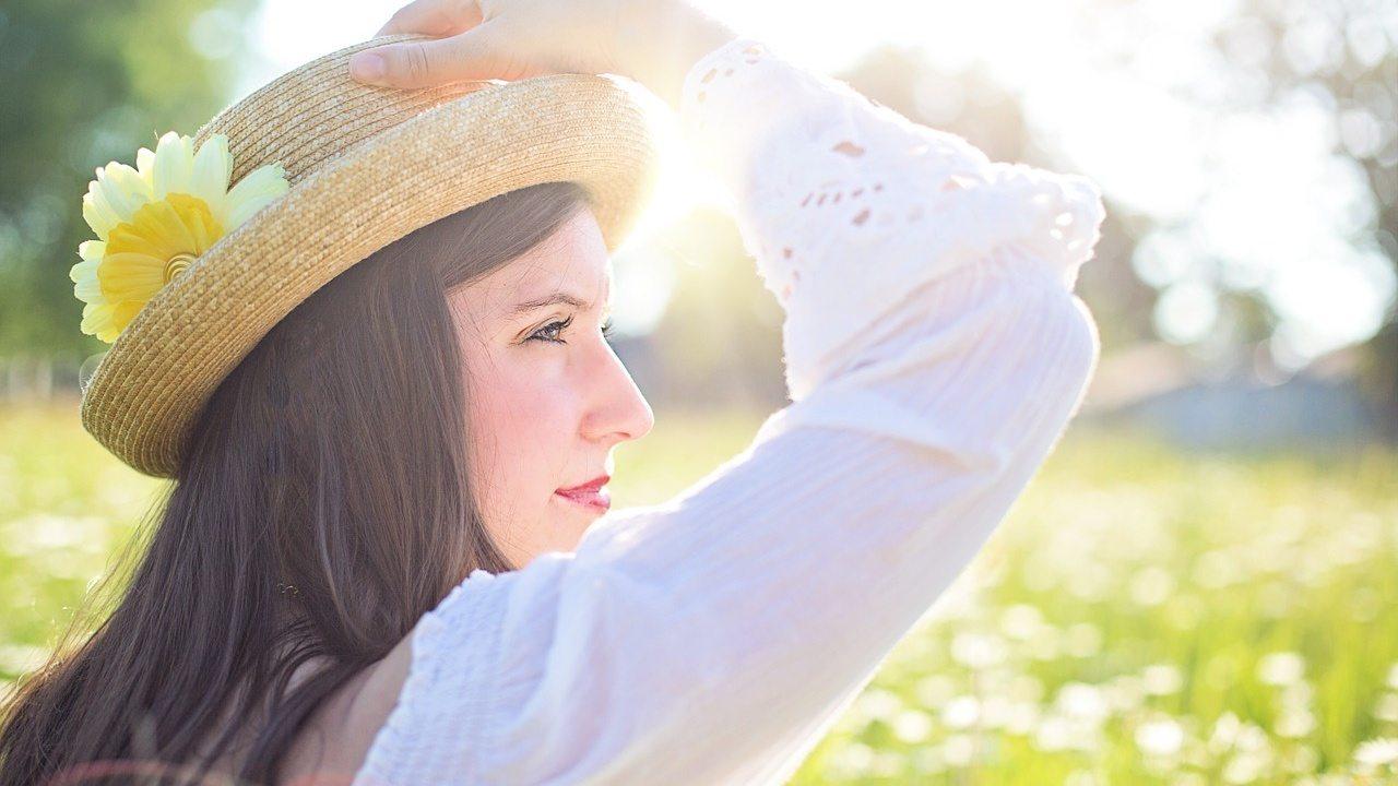 Donna con cappello contempla panorama