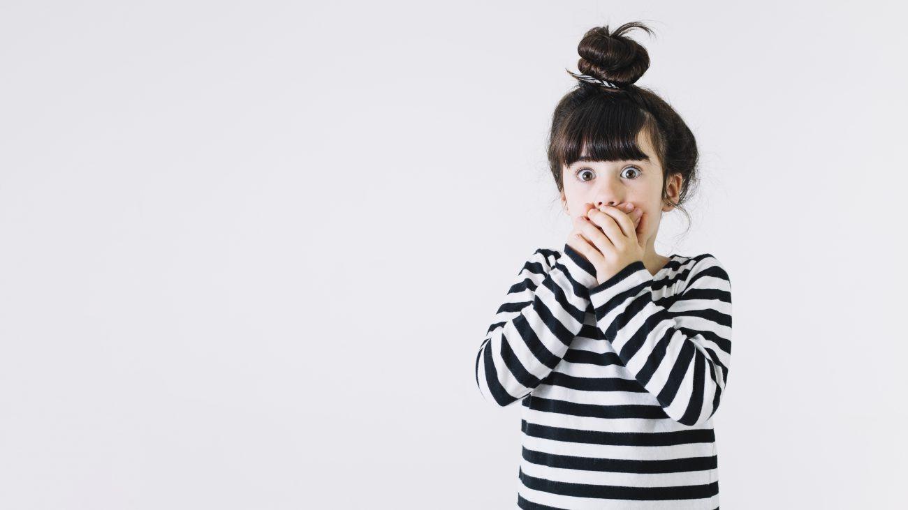 bambina sorpresa con mani davanti alla bocca
