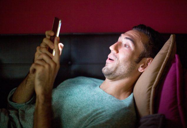 uomo con smartphone sorpreso